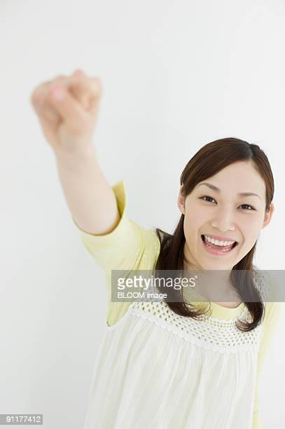 Young woman raising fist, portait