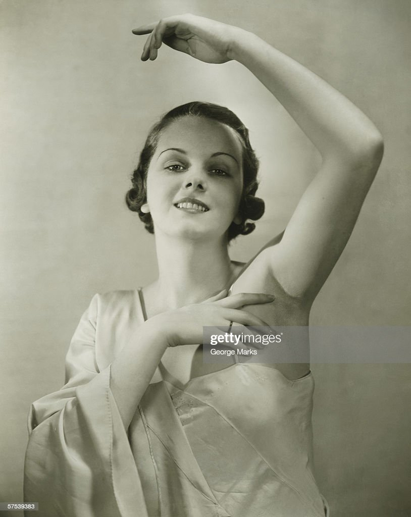 Young woman raising hand, posing in studio, (B&W), portrait : Stock Photo