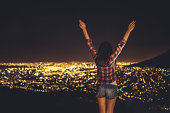 Young woman raising her arms up with city lights beyond