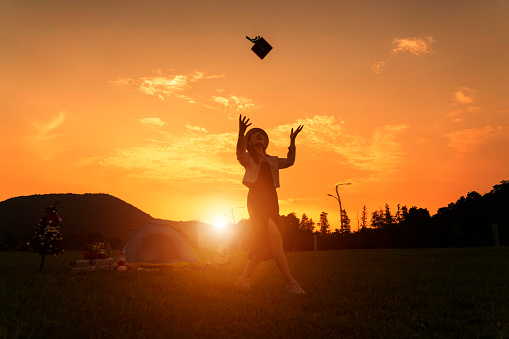 A young woman ran freely on the grass in the setting sun. The picture was beautiful. 1058652522