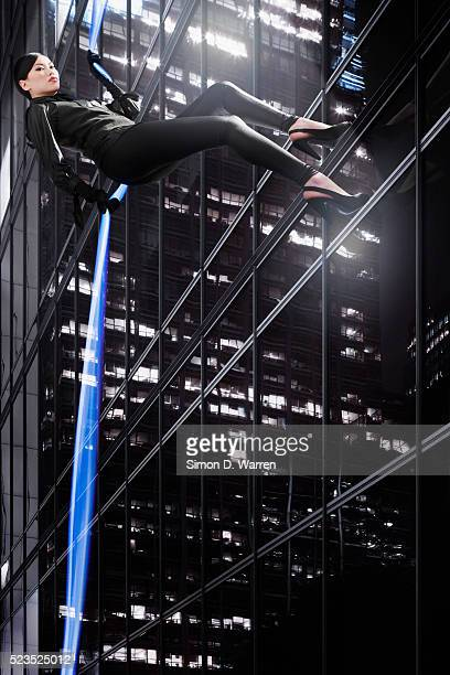 Young woman rappelling down an office building