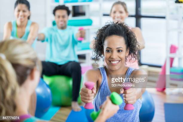 young woman reaches forward with hand weights during exercise class - hand weight stock pictures, royalty-free photos & images