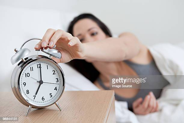 young woman reaching for alarm clock - waking up stock pictures, royalty-free photos & images