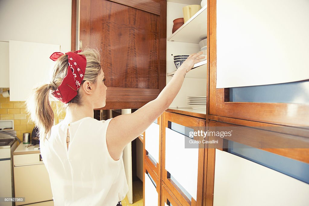 Young woman reaching for cupboard in vintage kitchen : Foto de stock