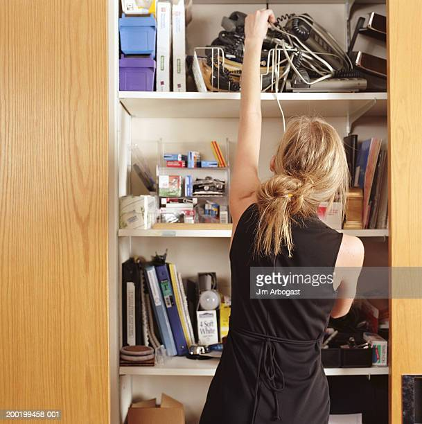 Young woman reaching for office supplies in closet, rear view