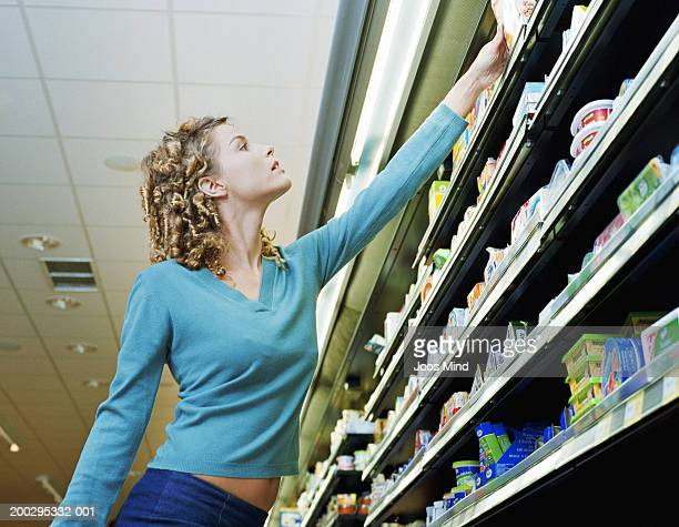 Young woman reaching for product on supermarket shelf, low angle view