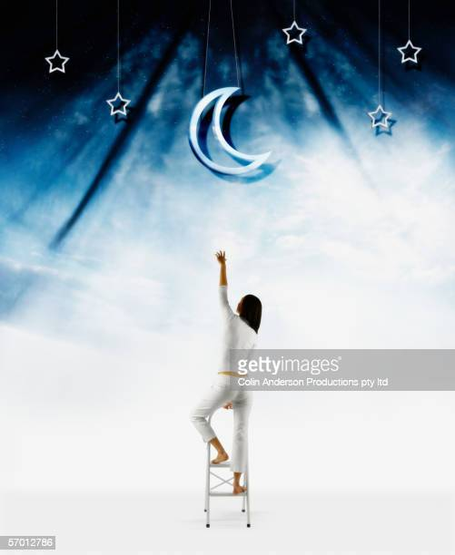 young woman reaching for the moon - ladder to the moon stock pictures, royalty-free photos & images