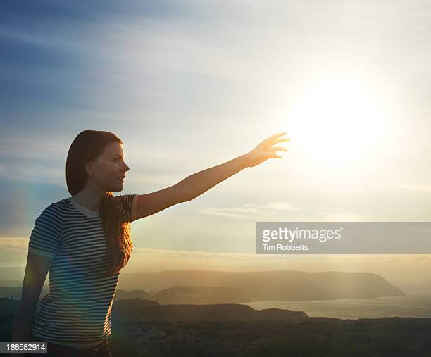 Young woman reaching for the sun next to the sea.