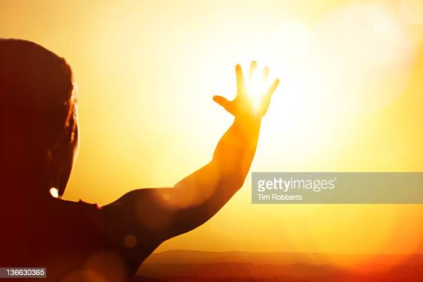 young woman reaching for the sun. - heat stock pictures, royalty-free photos & images