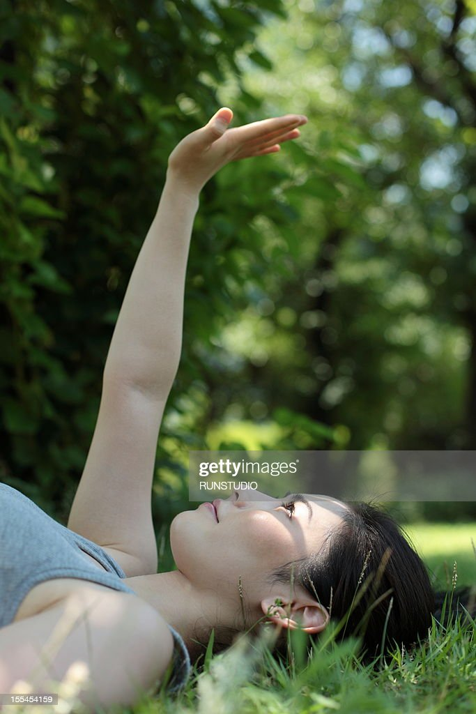 young woman reaching hand towards the sun : Foto de stock