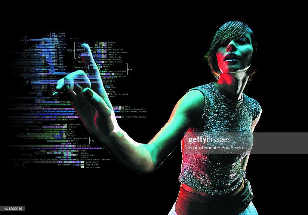 Young Woman Reaching Out to Push a Futuristic Touch Sensitive Computer Monitor Displaying Data : Foto de stock