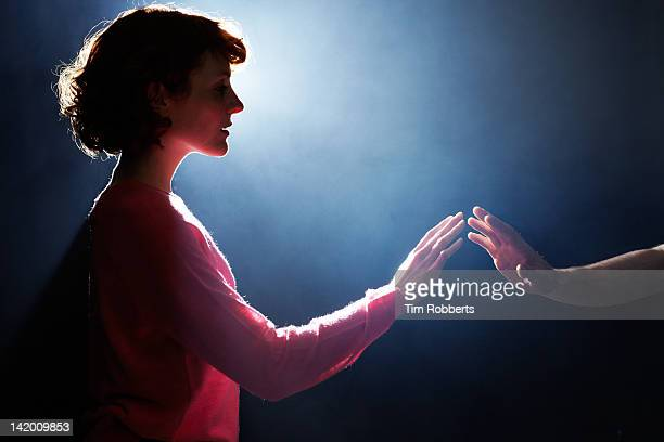 young woman reaching towards man. - reaching stock pictures, royalty-free photos & images