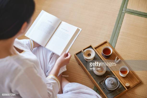 young woman reading a book and relaxing - 間 ストックフォトと画像
