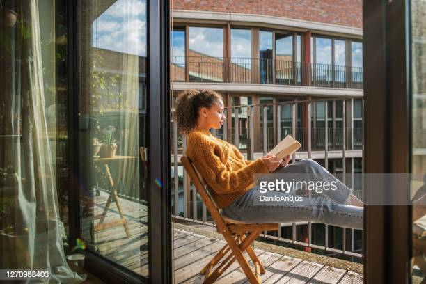 young woman reading a book at home - enjoyment stock pictures, royalty-free photos & images