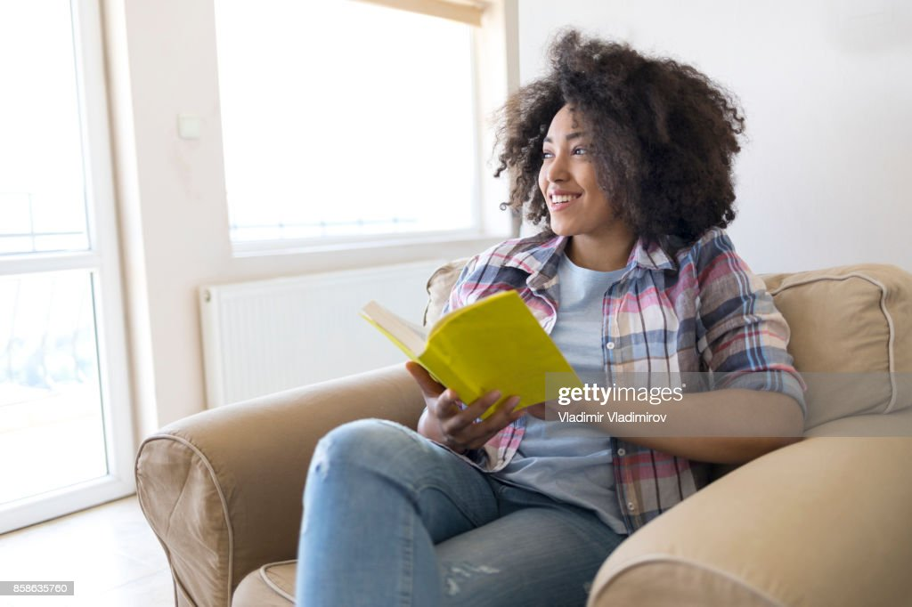 Junge Frau liest ein Buch wie zu Hause fühlen : Stock-Foto