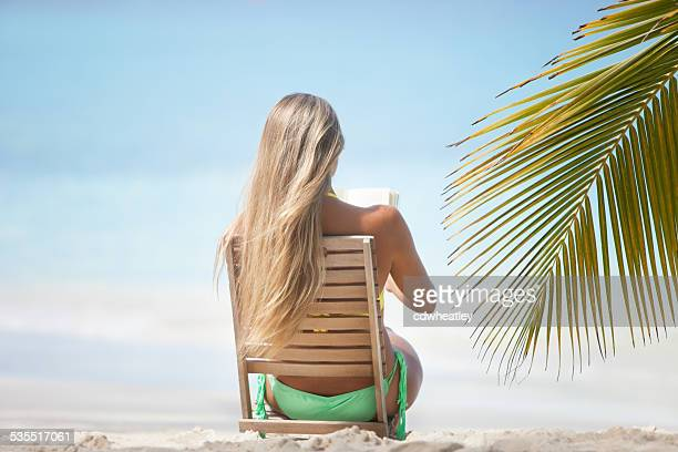 young woman reading a book at the Caribbean beach