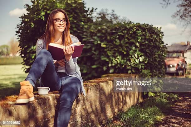 Mujer joven leyendo un libro en el campo