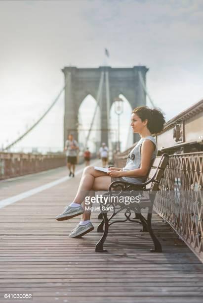 Young woman reading a book, Brooklyn Bridge