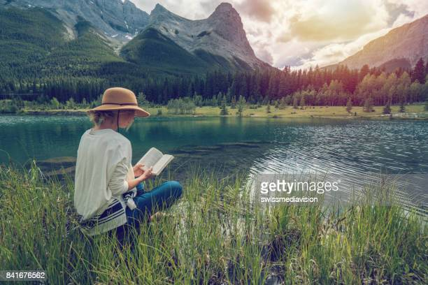 young woman reading a book by the lake - reading stock pictures, royalty-free photos & images