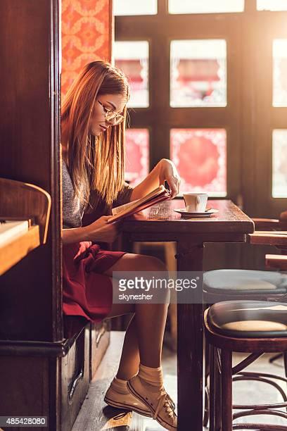 Mujer joven leyendo un libro en una cafetería.