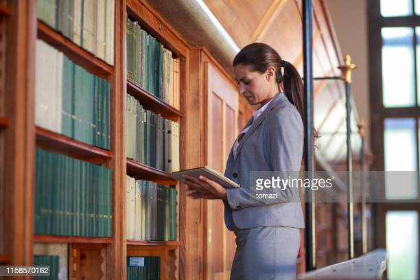 young woman reading a book in public library - legge foto e immagini stock