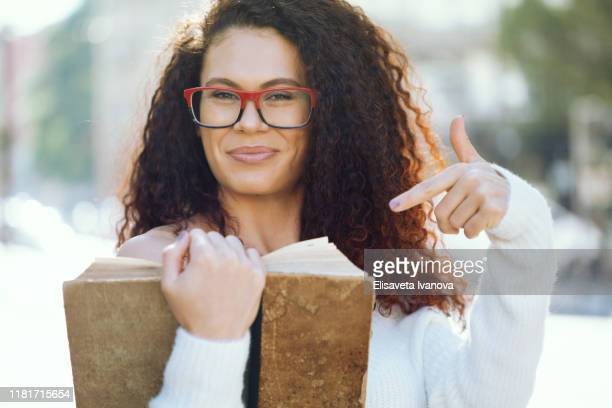 young woman reading a book in the park - literature stock pictures, royalty-free photos & images