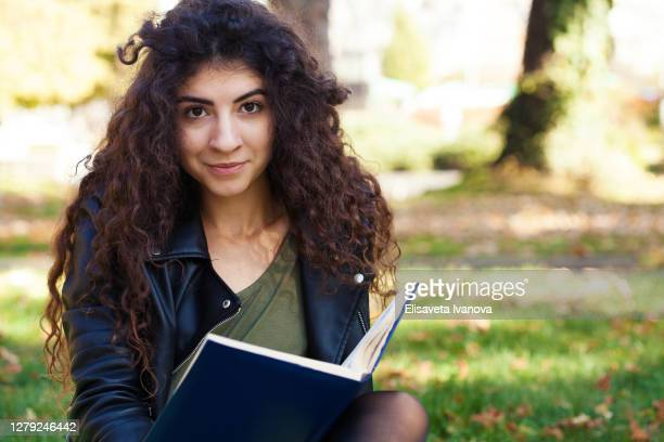 young woman reading a book in the park - poet stock pictures, royalty-free photos & images