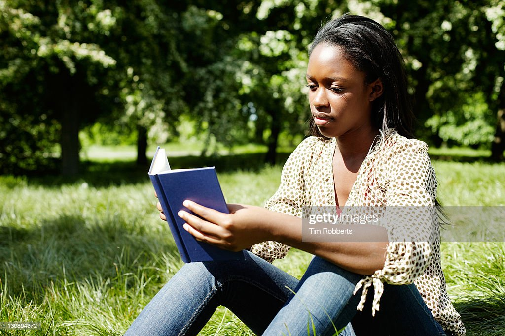 Young woman reading a book in the park. : Stock Photo