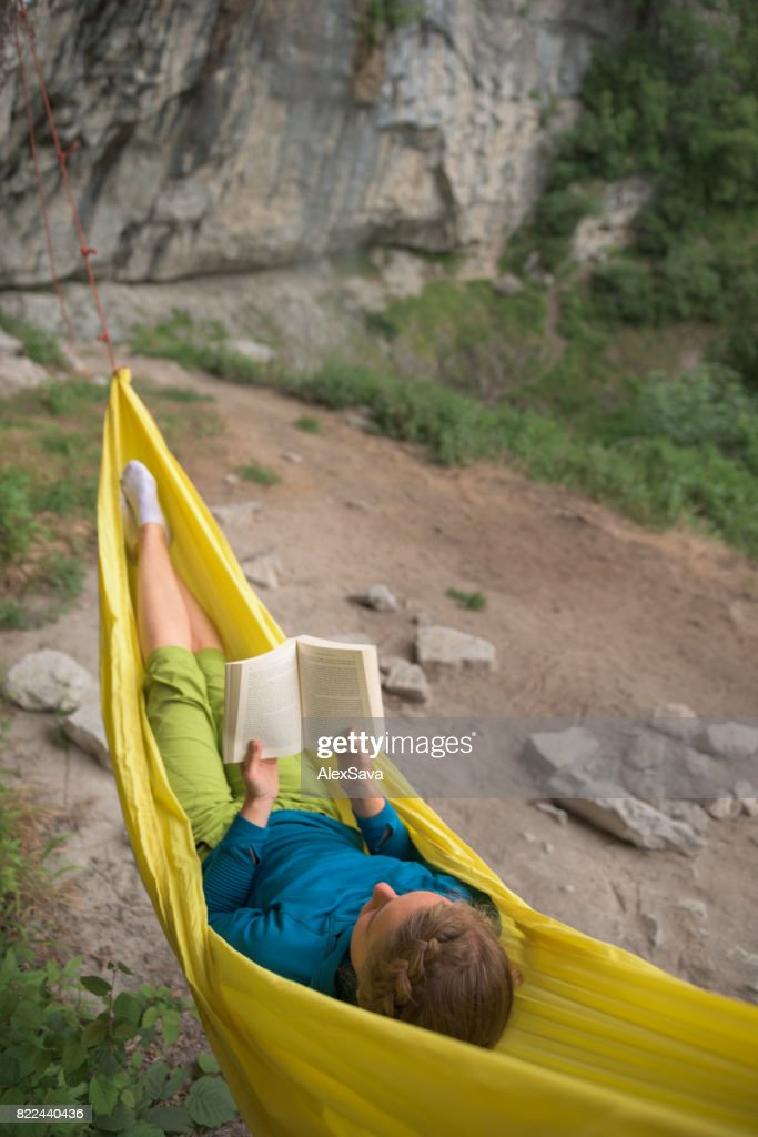 Young woman reading a book in yellow hammock outdoor in nature : Stock Photo