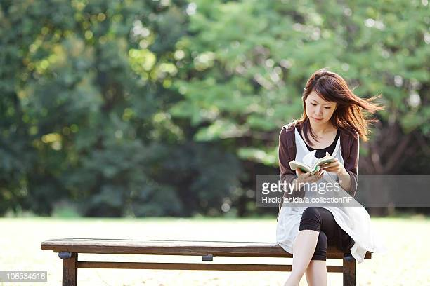 Young woman reading a book sitting on bench, Japan