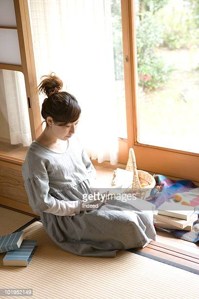 Young woman reading a book, sitting on tatami mat
