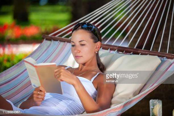 Young woman reading a book while relaxing on hammock in a peaceful garden during holiday