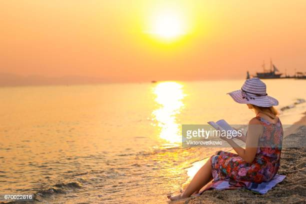 Young woman reading a book while relaxing on tropical beach