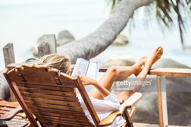 Young woman reading a book while relaxing on tropical island