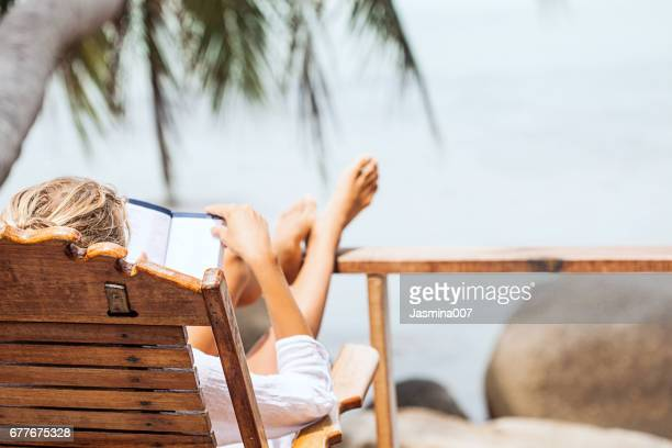 young woman reading a book while relaxing on tropical island - taking a break stock photos and pictures