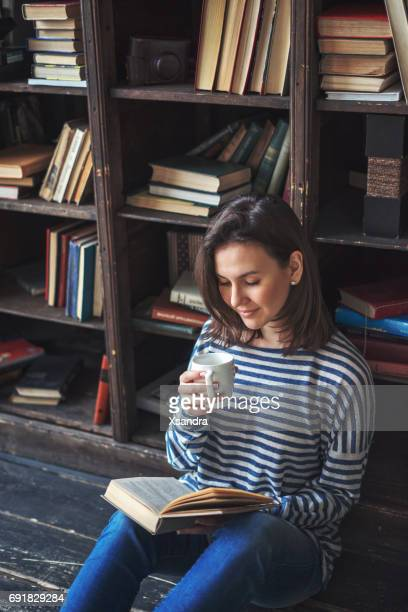 young woman reading a book with a cup of coffee - literature stock photos and pictures