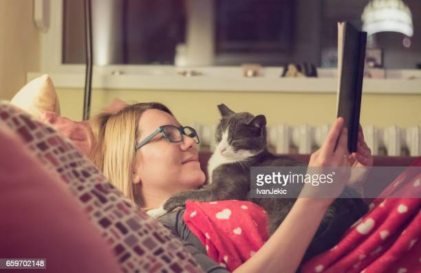 Young woman reading a book with her cat at night