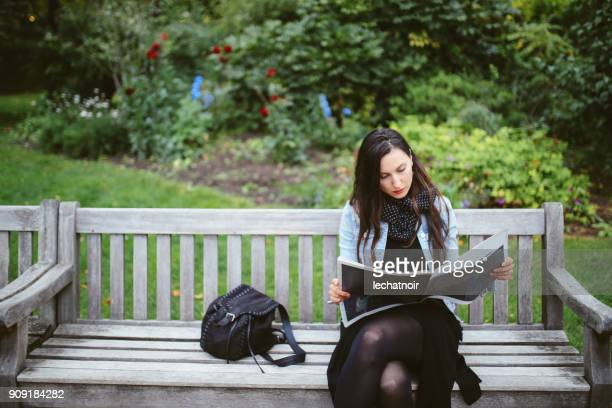 young woman reading a magazine in london public park - nature magazine stock pictures, royalty-free photos & images