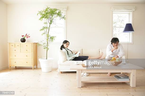 Young woman reading a magazine with a young man drinking a cup of tea