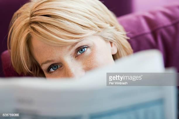 young woman reading a newspaper - delen begrippen stockfoto's en -beelden