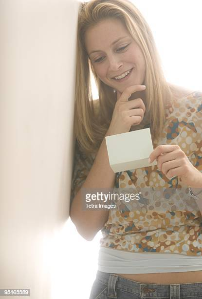 A young woman reading a note