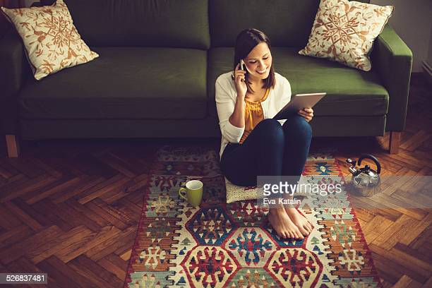 Junge Frau Lesen eines tablet und hören, Ihre E-Mails