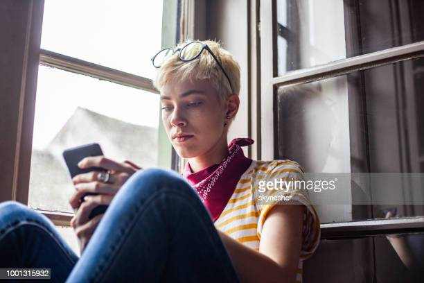 Young woman reading a text message on cell phone by the window.