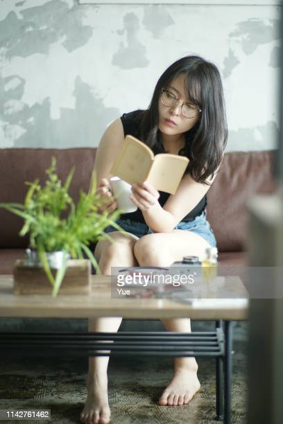 young woman reading at home - myopia stock photos and pictures