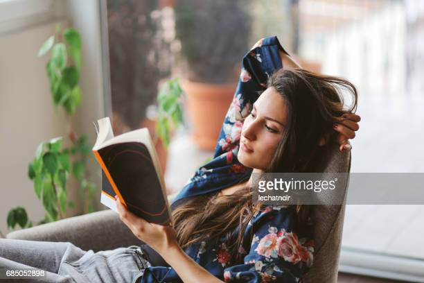 young woman reading at home - reading stock pictures, royalty-free photos & images