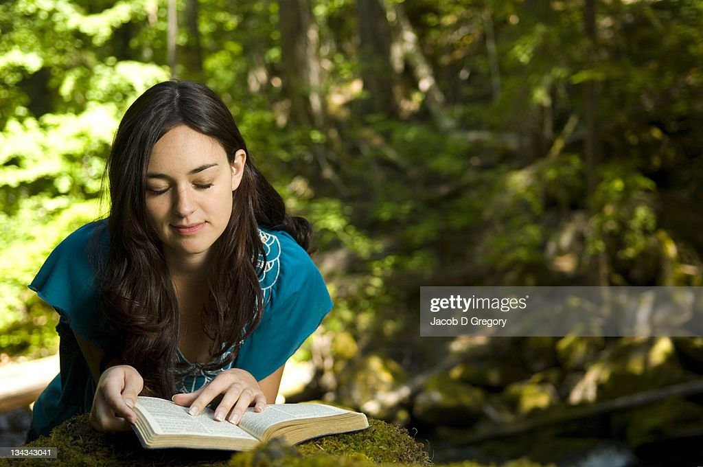 Young woman reading bible by stream : Stock Photo