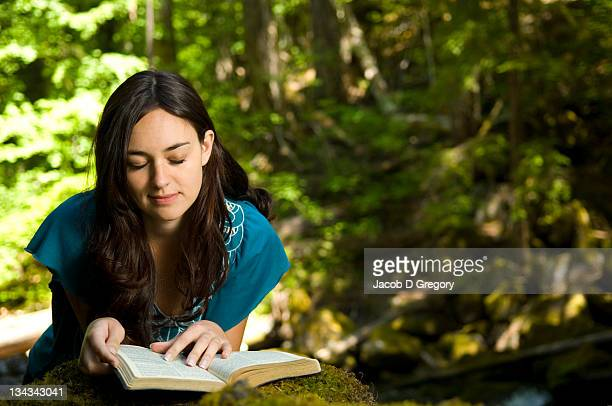 Young woman reading bible by stream