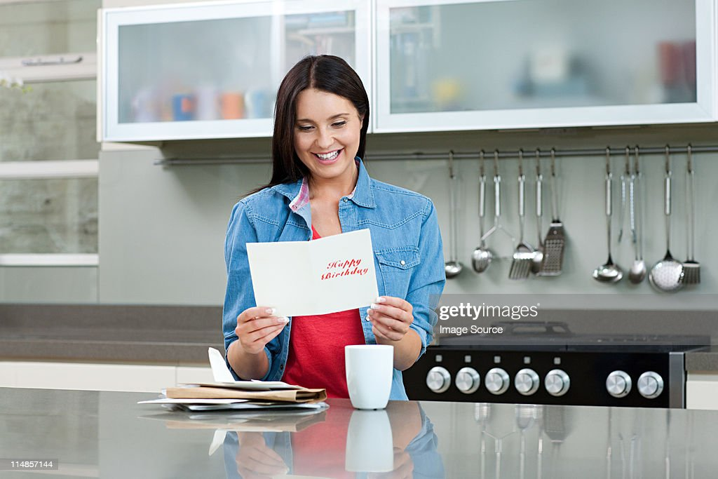 Young woman reading birthday card : Stock Photo