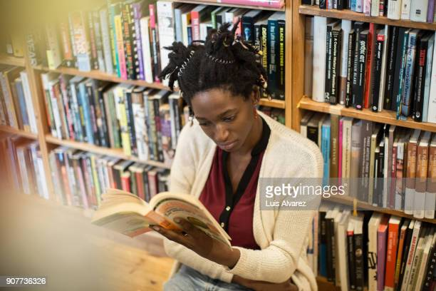 Young woman reading book against bookshelf