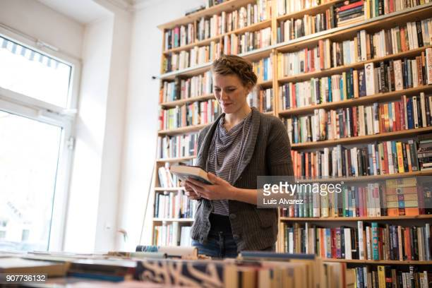 Young woman reading book at bookstore